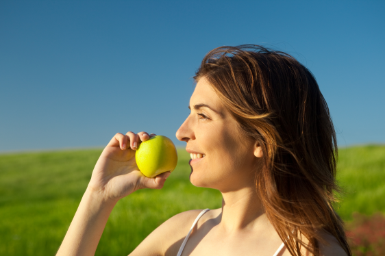 woman eating apple outside sunshine